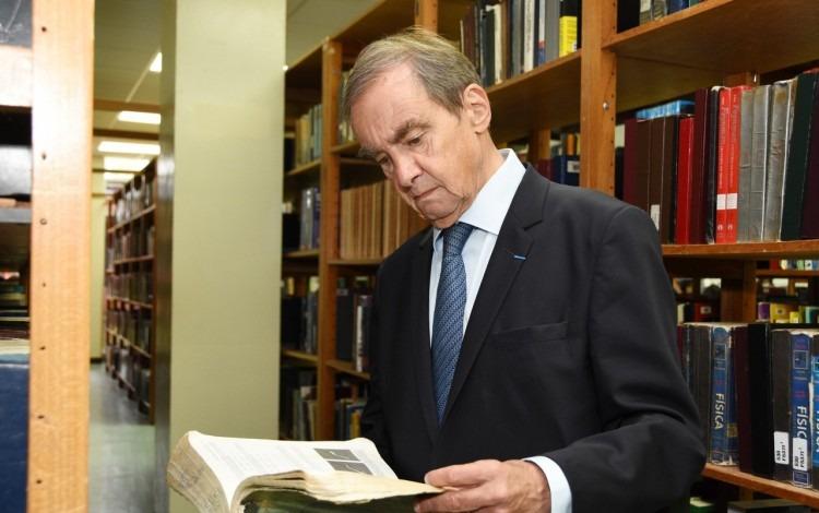 Hombre leyendo observando un libro.