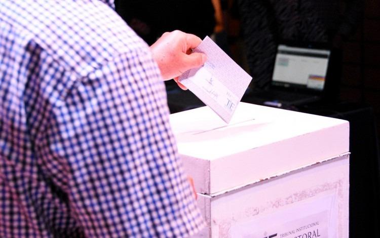 Persona depositando papeleta en urna