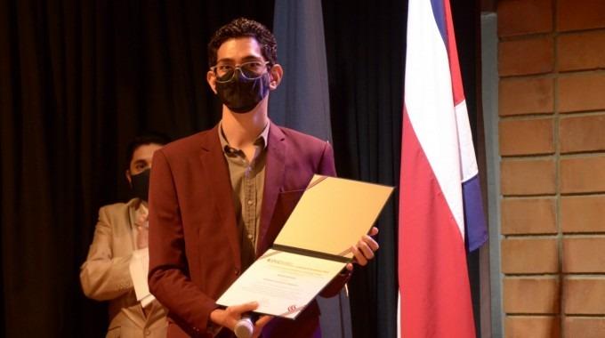 Miguel Alejandro Víctor Benavides sostiene en sus manos el certificado de acreditación de la carrera.