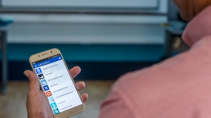 Imagen de una persona con un celular en la mano mostrando la herramienta Archibus.