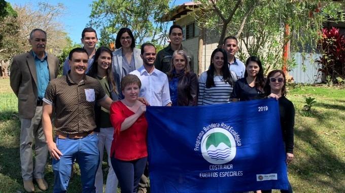 imagen de varias personas posando para la fotografía con la Bandera Azul Ecológica.