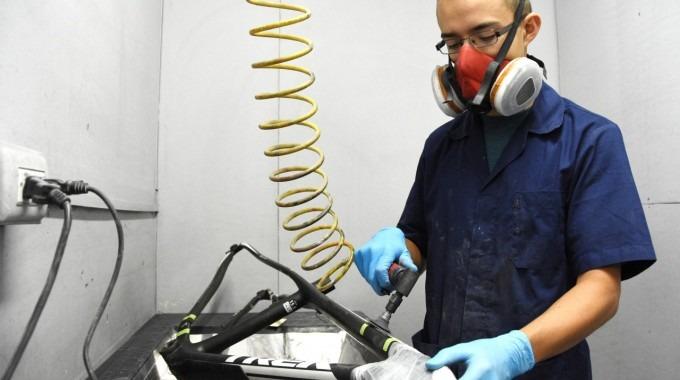 Trabajador de Difacom manipulando un marco de bicicleta.
