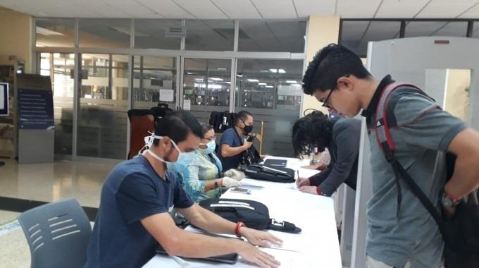 Estudiantes recogiendo computadora prestada.