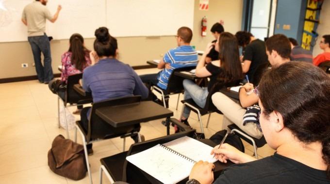 imagen de varios estudiantes en en aula recibiendo lecciones.