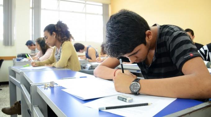 Imagen de varios estudiantes (hombres y mujeres) realizando un examen en un aula.