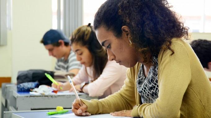 Imagen de una estudiante sentada en su pupitre dentro del aula.