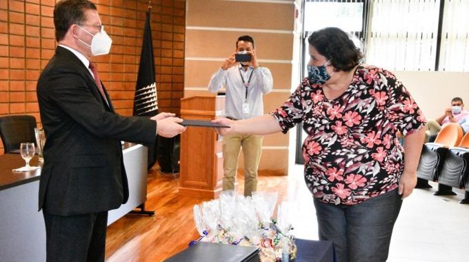 La estudiante recibe el título.