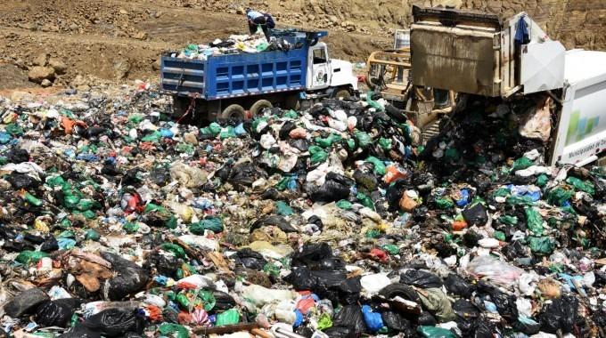 Imagen de un relleno sanitario con dos camiones de basura
