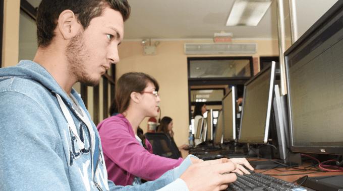 Imagen con varios estudiantes frente a la computadora.