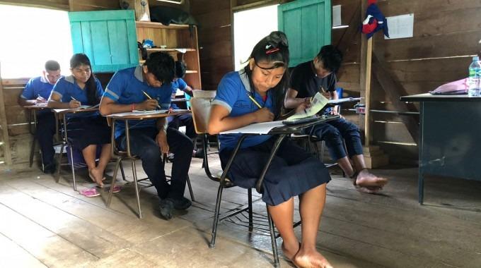 estudiantes indígenas en un escritorio haciendo examen.