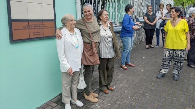 Las tres artistas sonríen, junto a la obra.