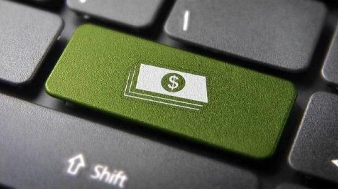 Teclado de computadora en el que la tecla enter tiene unos billetes y es de color verde