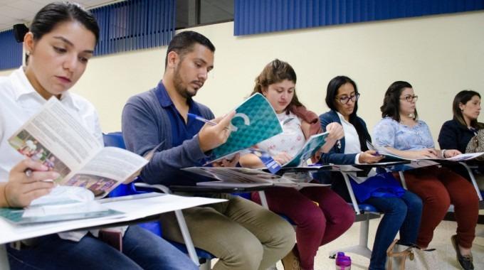 Imagen de varias personas sentadas viendo libros.