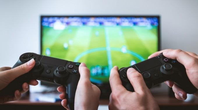 Dos pares de manos manejan controles de un videojuego que se aprecia en un monitor al fondo.