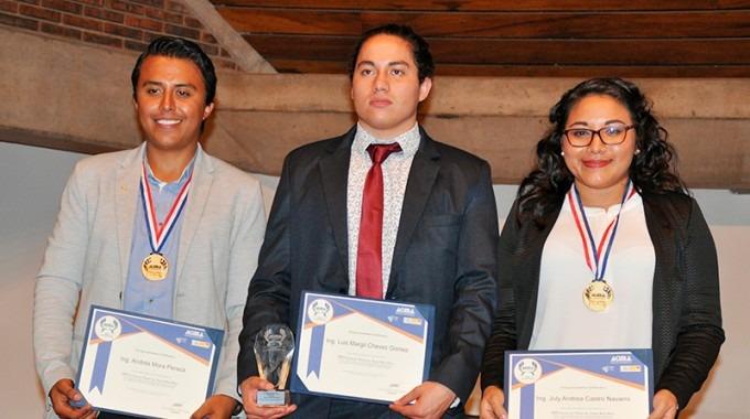 Tres estudiantes, dos hombres y una mujer, posan con sus títulos.