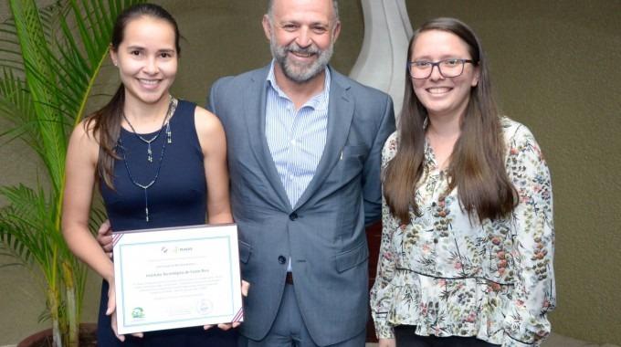 imagen de dos mujeres y un hombre posando para la fotografía con un reconocimiento que ganó el TEC.