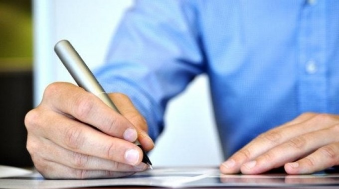 persona con un lapicero escribiendo