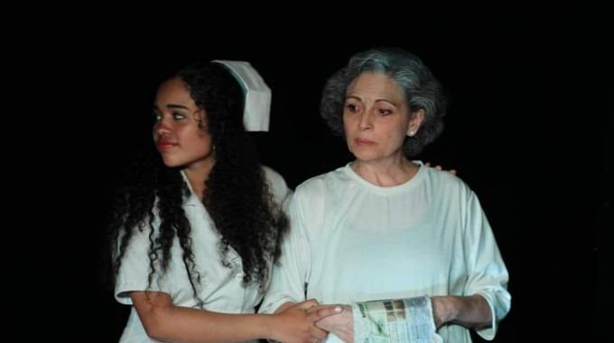 La fotografía muestra una de las escenas de la obra, donde una enfermera sostiene a una interna.