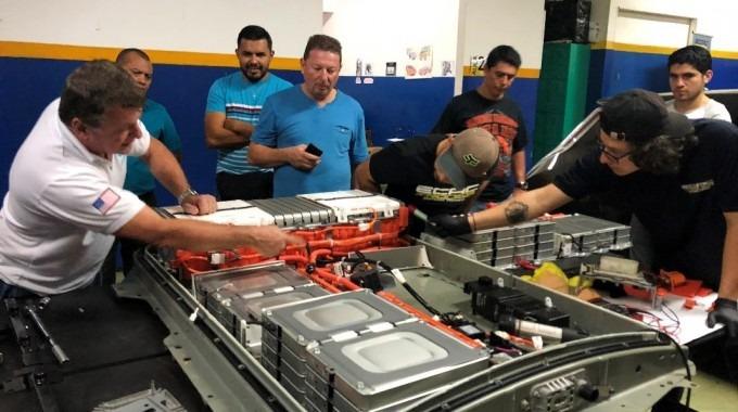 Varios jóvenes y profesores alrededor de unas baterías de automóvil.