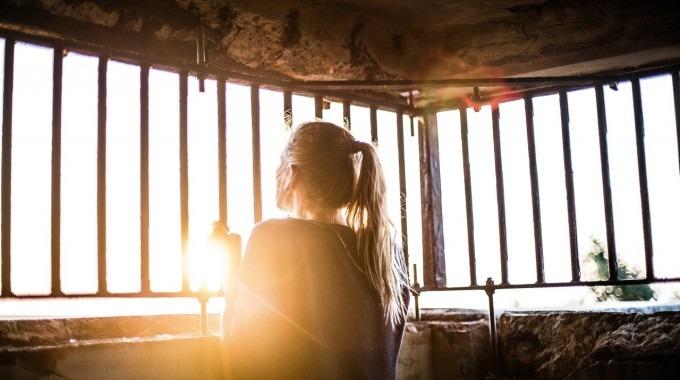 Mujer mira a través de las rejas de su casa