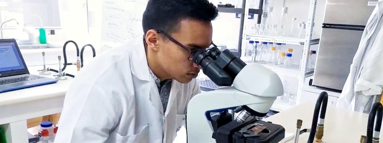 La imagen muestra a José Pablo en el laboratorio viendo a través del microscopio.