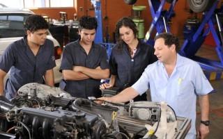 Tres estudiantes observan al profesor explicarles partes de un motor.