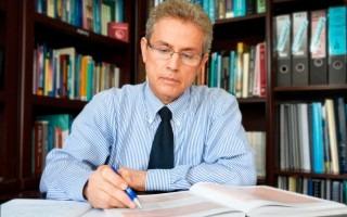 Hombre con corbata y lapicero en mano escribe en libro