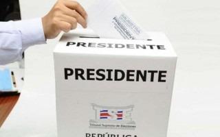 Una mano ingresando un voto en la urna.