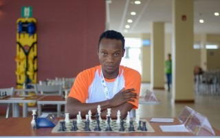 Godwell Manda frente a un tablero de ajedrez.