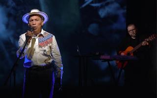 El cantante frente al micrófono, con sombrero. Al fondo, lo acompaña un músico con guitarra.