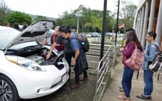 Un grupo de estudiantes observan un auto eléctrico.