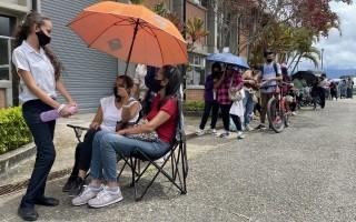 Personas haciendo fila con sombrillas para protegerse del sol.