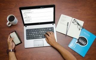 computadora, libreta y mano