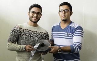 Imagen de dos hombres mostrando una cinta conductora de electricidad.