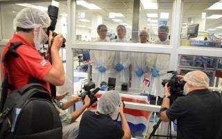 Tres fotógrafos frente a los ingenieros, separados por un vidrio. Los investigadores visten de bata de laboratorio.