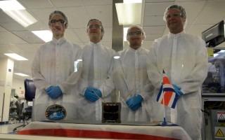 Los cuatro especialistas, tras un vidrio, con el satélite al frente.