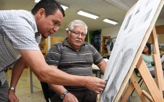 Un adulto mayor aprende a dibujar con la ayuda del profesor.