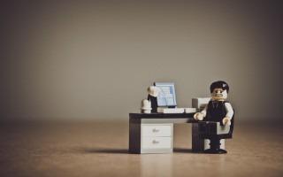 Figura de LEGO de un empresario desesperado frente a su escritorio