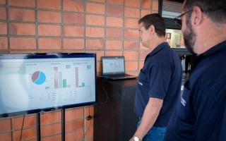 Imagen de los hombres observando la pantalla con los datos de la cantidad de votos realizados.