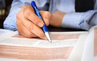Imagen de un hombre, con un lapicero, revisando un documento.
