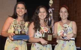 Imagen de tres mujeres con un trofeo