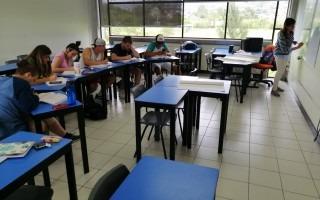 Estudiantes sentados en el aula recibiendo la clase