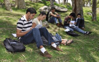Cinco estudiantes del TEC se encuentran (sentados) estudiando, en la zona verde de esta Institución  Son cuatro  hombres y una mujer.
