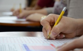 Imagen de una estudiante realizando el examen de admisión. En la fotografía se detalla la mano  con el lápiz.