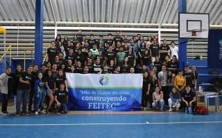 """Unos 30 estudiantes con una valla que dice """"Más de cuatro décadas construyendo Feitec""""."""