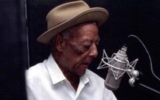 Imagen de un hombre de piel morena frente a un micrófono. El hombre es un músico limonense.