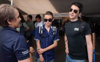 Dos jóvenes escuchando la información  de las becas que ofrece el TEC. Le explica una funcionaria del TEC