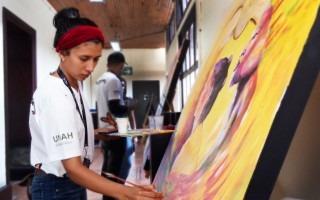 Imagen de una estudiante hondureña pintando en Casa de la Ciudad.