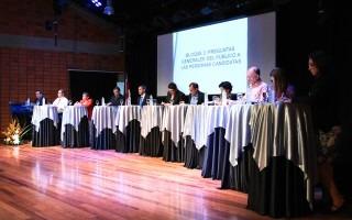 Los diez candidatos en fila, cada uno en una mesa.