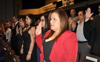 Imagen de varias personas levantando la mano derecha durante la juramentación.